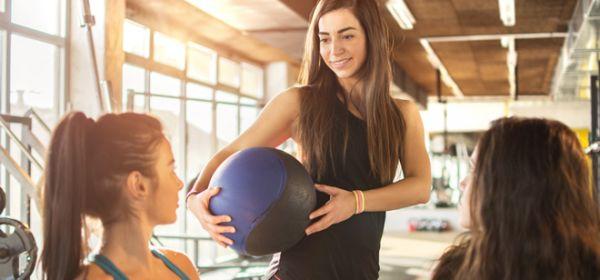Frau mit Medizinball unterhält sich mit zwei anderen Frauen
